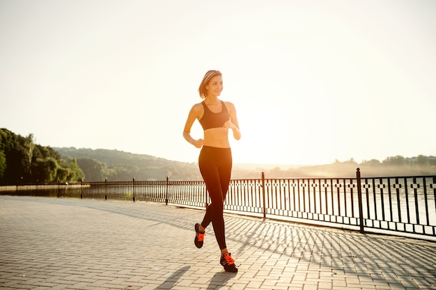 Running woman. runner jogging in sunny bright light. female fitness model training outside in park