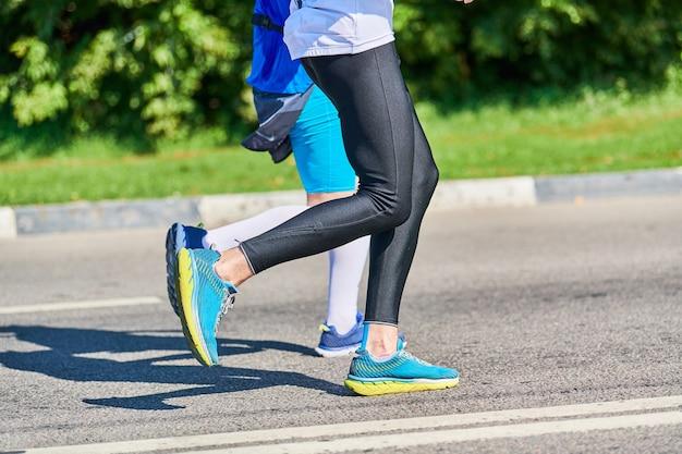 Бегущие женщины. спортивные женщины бегают трусцой в спортивной одежде на городской дороге.