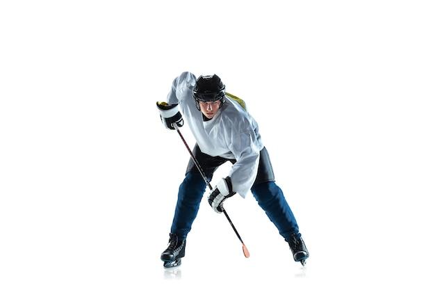 In esecuzione. giovane giocatore di hockey maschio con il bastone sul campo da ghiaccio e sfondo bianco. sportivo che indossa attrezzature e pratica del casco. concetto di sport, stile di vita sano, movimento, movimento, azione.