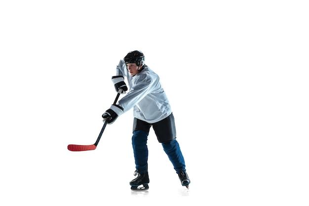 달리는. 아이스 코트와 흰색 배경에 막대기로 젊은 남자 하키 선수. 장비와 헬멧 연습을 착용하는 스포츠맨. 스포츠, 건강한 라이프 스타일, 운동, 운동, 행동의 개념.