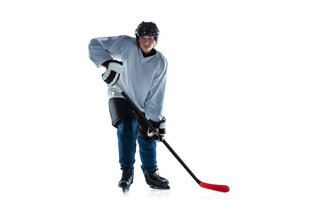 ランニング。アイス コートと白い背景にスティックを持つ若い男性のホッケー選手。スポーツマン着用の機器とヘルメットの練習。スポーツのコンセプト、健康的なライフスタイル、動き、動き、行動。