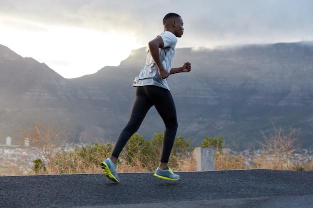 スポーツウェアで若い男を走らせ、ジョギング運動をし、持久力を練習し、山の近くで新鮮な空気を楽しんでいます。フィットネス、モーション、健康的なライフスタイルのコンセプト。朝のすごい澄んだ青い空。