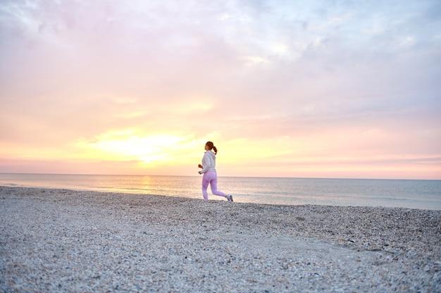 Бегущая молодая женщина на пляже вдоль морского побережья ранним утром во время восхода солнца