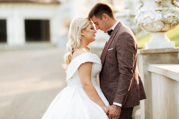 夕暮れ時の森の緑の野原でウェディングドレスとスーツで愛情のある流行に敏感なカップルと結婚しました。幸せな花嫁と花runningを歩いて実行し、夏の草原で踊ります。