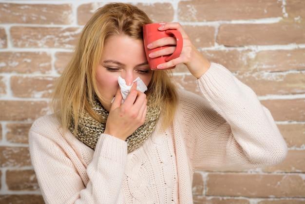 風邪の鼻水症状。風邪を治すためのヒント。救済策は風邪を早く打つのに役立つはずです。女性はくしゃみがひどく気分が悪い。風邪やインフルエンザの治療法。スカーフの女の子はティッシュやナプキンを持って頭痛に苦しんでいます。
