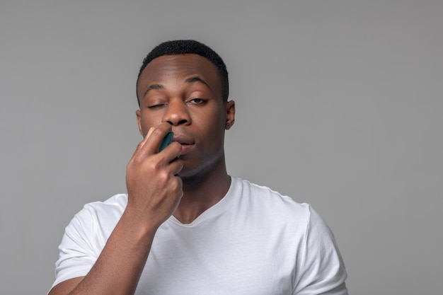 Runny nose, treatment. unhappy young adult dark skinned man in white tshirt with spray near nose treating cold