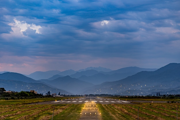 Runway at the airport against the backdrop of the mountains in the evening