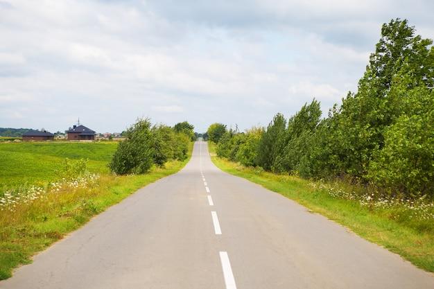Rural, asphalt road in green field