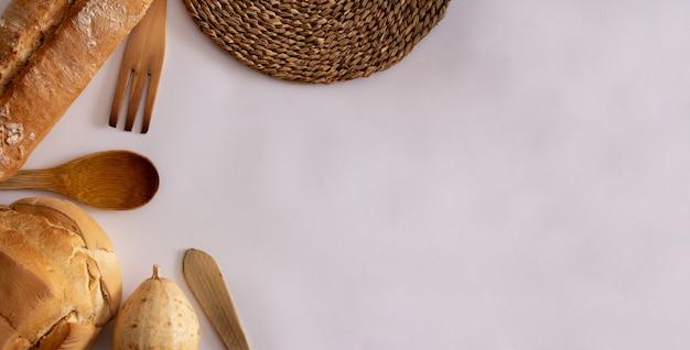 カボチャと木製のフォークと籐のテクスチャーを備えたおたまを備えた田舎のパン。フラットレイコピースペース