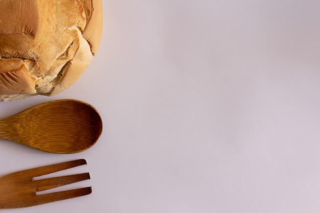 白い背景の上の木製のフォークとおたまと田舎のパン。上面図。フラットレイ。スペースをコピーします。