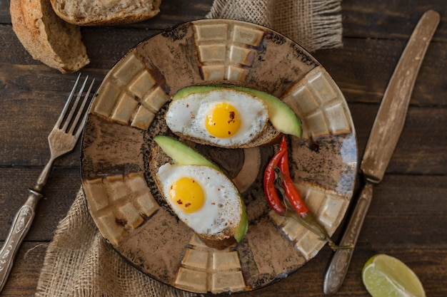 Rural breakfast toast with fried eggs and avocado on wooden board over brown background, top view.