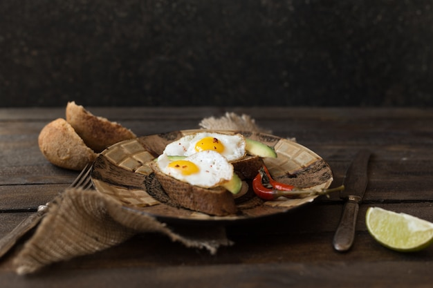 Rural breakfast toast with fried eggs and avocado on wooden board