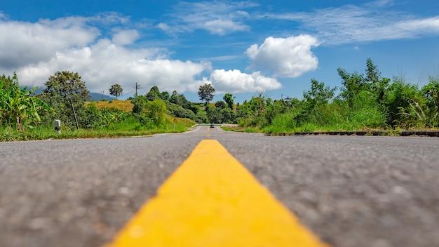 青空の下のラッシュグリーンフォレスト山脈の田舎の田舎道