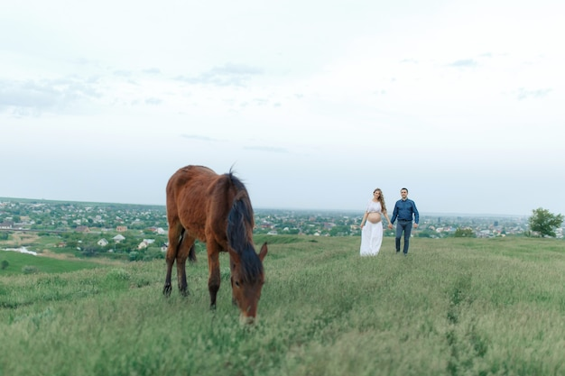 Rural couple on a green meadow communicates with animals. pregnant wife. therapy and relaxation for pregnant women.