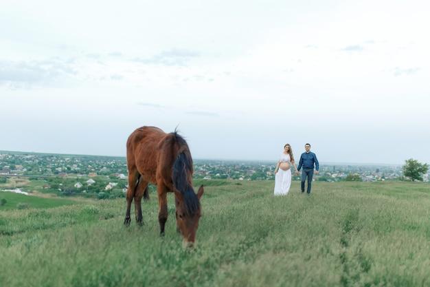 緑の牧草地の田舎のカップルは動物と通信します。妊娠中の妻。妊娠中の女性のための治療とリラクゼーション。
