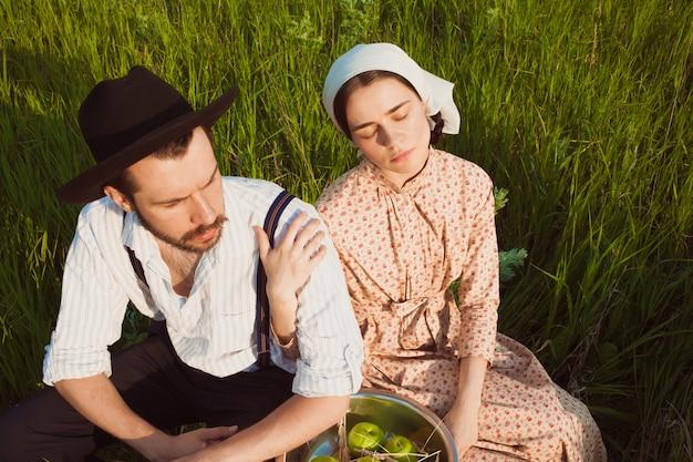Rural couple sitting in field