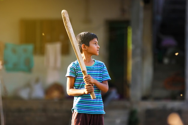 Rural indian child playing cricket on ground