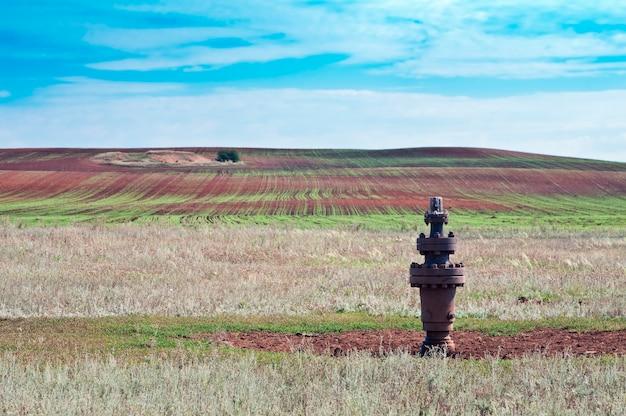 Сельский пейзаж, консервная нефтяная скважина на переднем плане
