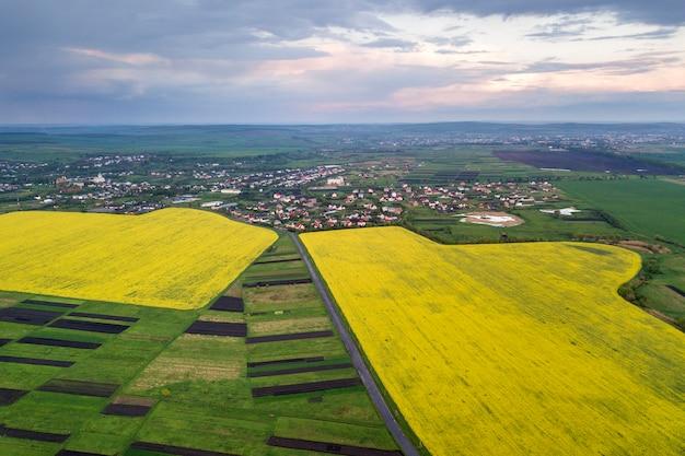 Сельский пейзаж на весенний или летний день. аэрофотоснимок зеленых, распаханных и цветущих полей, крыши домов на солнечный рассвет. беспилотная фотография.