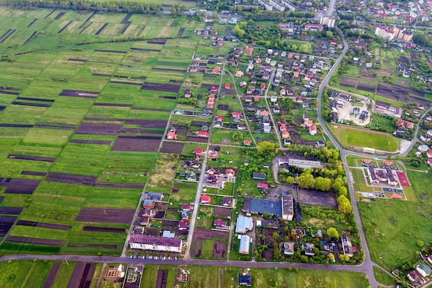Rural landscape on spring or summer day. aerial view of green and plowed fields, village or town house roofs and roads on sunny dawn. drone photography.