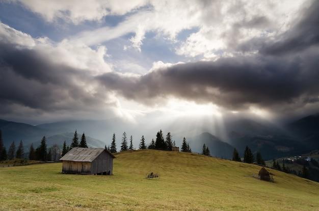 극적인 하늘과 시골 풍경입니다. 산 마을의 가을. 초원에 나무 오두막입니다. 폭풍 구름과 태양 광선입니다. carpathians, 우크라이나, 유럽
