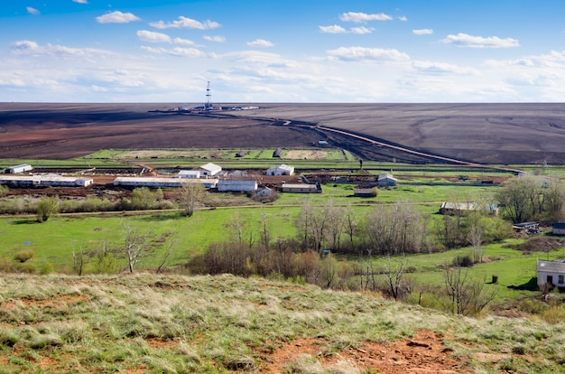 Rural landscape with a drilling tower on the horizon. view from above