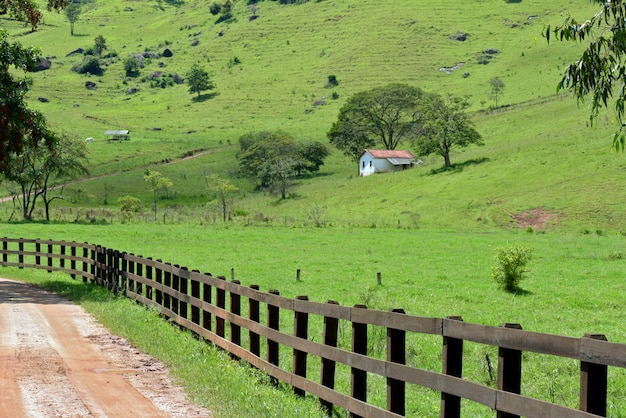 Rural landscape with foreground fence and small house in the background. minas gerai, brazil
