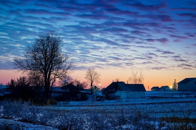 日の出の間の木や建物のシルエットのある田園風景_