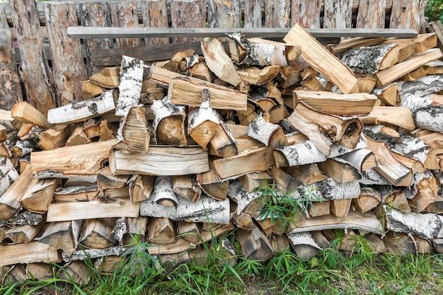 시골 생활 울타리 근처에는 큰 자작나무 장작 더미가 있습니다. 장작의 자연 배경