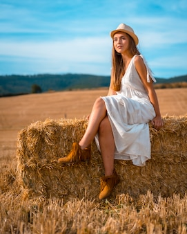Rural lifestyle, portrait of a young caucasian blonde farmer in white dress and a white hat in summer