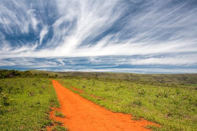 Сельская оранжевая грунтовая дорога с голубым небом и далеким горизонтом