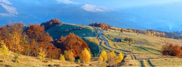 Сельская дорога и красочные деревья на осеннем склоне горы.