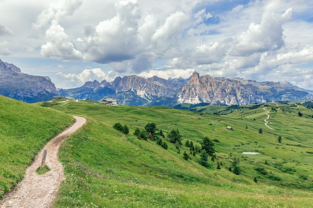 Rural road in green alpine valley with view of italian dolomites.