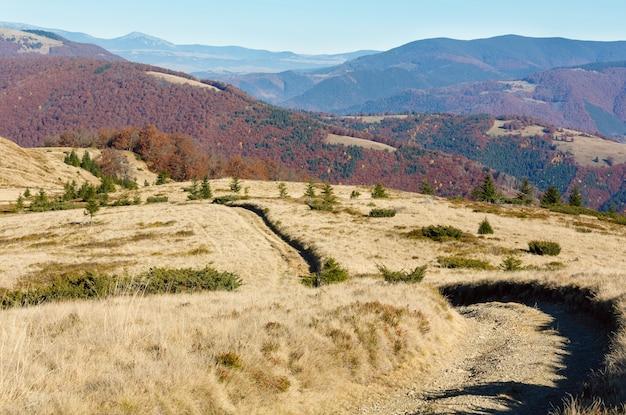 Сельская дорога осенью горы и красочные деревья на склонах.