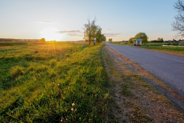 Rural road in the village next to the field at sunset