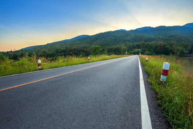 Rural road with scenic view of the reservoir huay tueng tao with mountain range forest