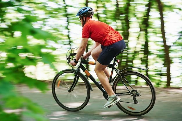 田舎のシーン。自転車のサイクリストは晴れた日に森のアスファルト道路に
