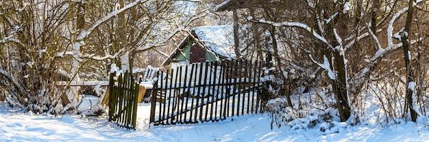 雪に覆われた木々、柵、庭の古い家のある田園風景