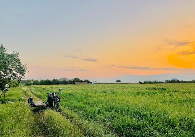 緑の野原の人けのない村の道路にサイドカーと田舎の村の風景の古いオートバイ
