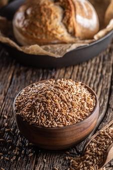 신선한 밀가루를 위해 갈 준비가 된 밀 곡물로 가득 찬 시골 나무 그릇. 백그라운드에서 바삭바삭한 효모 빵 덩어리입니다.