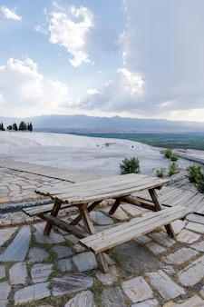 Деревенская деревянная скамейка для пикника на холме с зеленой травой в горном пейзаже иераполиса
