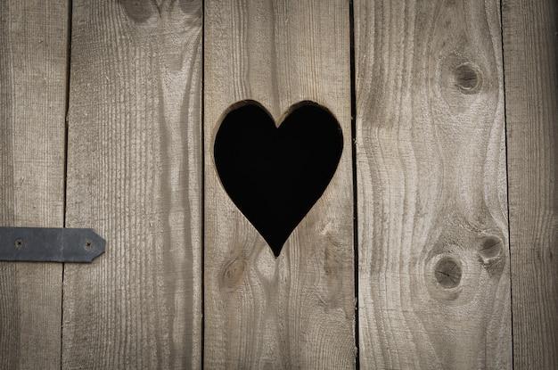 Сельский деревянный туалет, сердце на доске