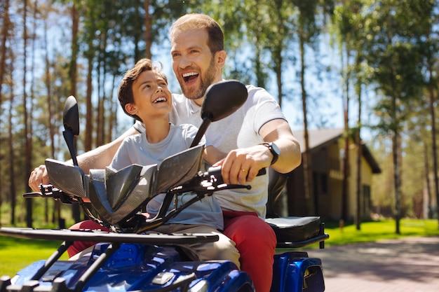 アドレナリンのラッシュ。満足のいく若い父親が笑顔で息子と一緒に全地形対応車を運転