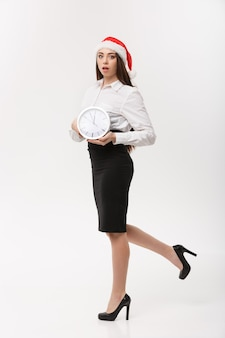 Rush time concept - beautiful young caucasian woman running with clock isolated on white.