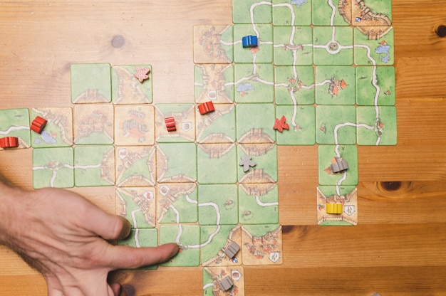 Russia, december 2020: hand of man playing the board game carcassonne on the table at night, top view