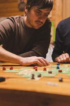 Россия, декабрь 2020 года: двое друзей-мужчин развлекаются, играя в настольную игру каркассон поздно вечером или ночью. мужские руки и игровые карты и фишки на столе