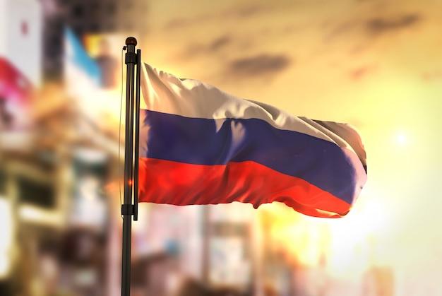 Флаг россии против города размытый фон при восходе солнца