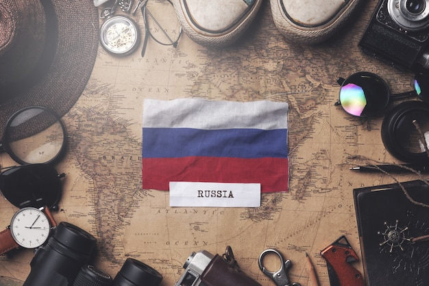 Флаг россии между аксессуарами путешественника на старой винтажной карте. верхний выстрел