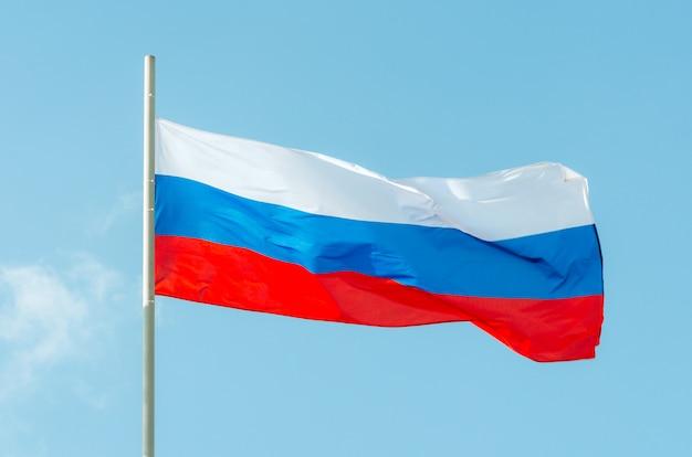 Флаг россии. размахивая красочный флаг россии на голубое небо.