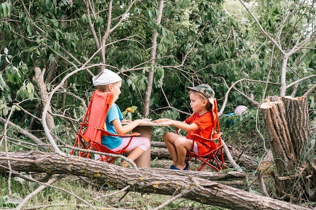 Russia, july 2020 - little kids, a boy and a girl friends have a fun picnic and eat among fallen trees in the summer in the village in the countryside on vacation